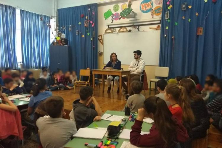 Η κα Μαρία Ηλιοπούλου και ο Κωνσταντίνος μπροστά σε μαθητές Δημοτικού