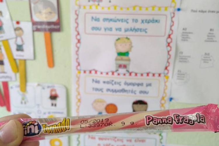 Τα δάχτυλα του Κωνσταντίνου κρατάνε ένα ζαχαρωτό με φόντο τον γεμάτο ζωγραφίες τοίχο μιας σχολικής τάξης