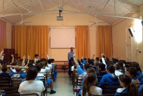 Ο Βαγγέλης χαμογελάει στα παιδιά που έχουν σηκωμένα τα χέρια τους για να κάνουν ερώτηση