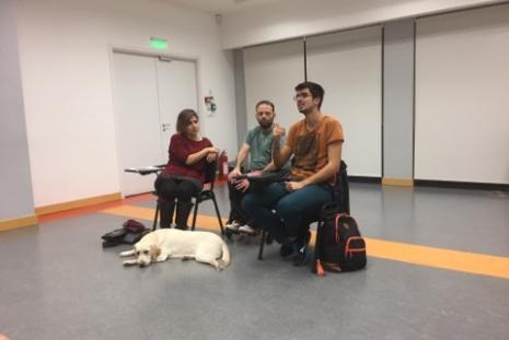Ο Κωνσταντίνος, Ο Παναγιώτης, η Θάλεια και ο εκπαιδευόμενος σκύλος οδηγός από το Κέντρο Σκύλων Οδηγών Ελλάδος, Νίκη, κάθονται όλοι μαζί και συνομιλούν με το κοινό.