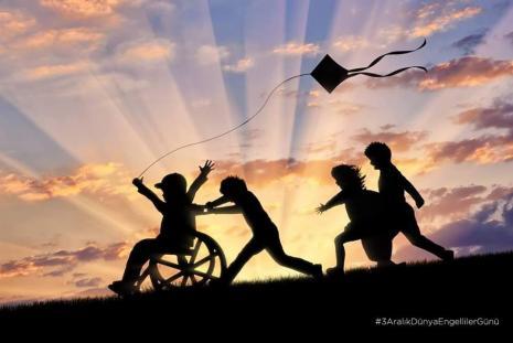 Σκοτεινές φιγούρες, τέσσερα παιδιά παίζουν χαρούμενα, το ένα με αναπηρικό αμαξίδιο και ένας χαρταετός από πάνω τους